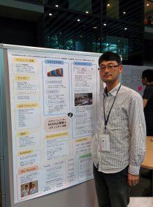 PyCon JP 2016 ポスターの前に立つ西本